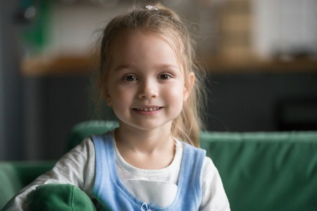 Foto de Portrait of cute little girl indoors, happy funny pretty child with sincere smiling face looking at camera, adorable positive cheerful kid posing at home on sofa, beautiful preschool model headshot - Imagen libre de derechos