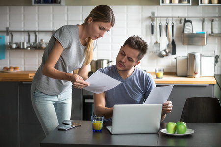 Photo pour Serious millennial couple worried about high utility bills or rent payment reading papers in kitchen, confused husband and wife discussing bad news in bank loan document having debt financial problem - image libre de droit