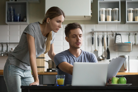 Photo pour Young serious couple discussing papers with laptop, man and woman roommates or husband and wife checking rent or domestic bills to pay online, planning budget or analyzing financial expenses together - image libre de droit
