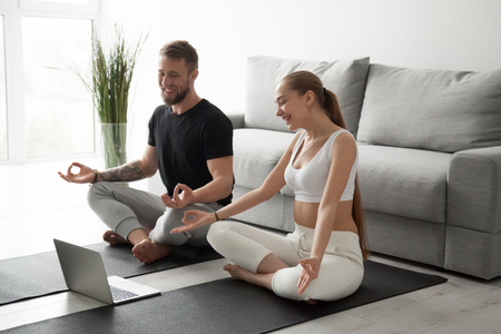 Foto de Smiling millennial couple practice yoga on mats at home watching video tutorial on laptop, excited man and woman sit in lotus position meditating repeating online instructions by coach on computer - Imagen libre de derechos