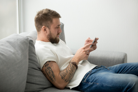 Photo pour Focused millennial man sitting on cozy couch holding tablet reading online news or checking mail, lazy guy relaxing on sofa playing app games or downloading new applications, male browsing web - image libre de droit