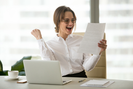 Foto de Excited satisfied businesswoman celebrating business success motivated by great financial work result in report, cheerful employee reading letter or notice with good news happy about job promotion - Imagen libre de derechos