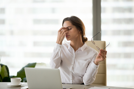 Foto de Fatigued businesswoman taking off glasses tired of computer work, exhausted employee suffering from blurry vision symptoms after long laptop use, overworked woman feels eye strain tension problem - Imagen libre de derechos