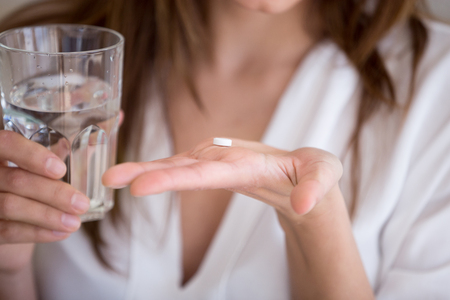 Foto de Woman holding pill and glass of water in hands taking emergency medicine, supplements or antibiotic antidepressant painkiller medication to relieve pain, meds side effects concept, close up view - Imagen libre de derechos