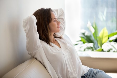 Foto de Relaxed calm woman resting breathing fresh air feeling mental balance enjoying wellbeing at home on sofa, satisfied young lady taking pleasure of stress free weekend morning stretching on couch - Imagen libre de derechos