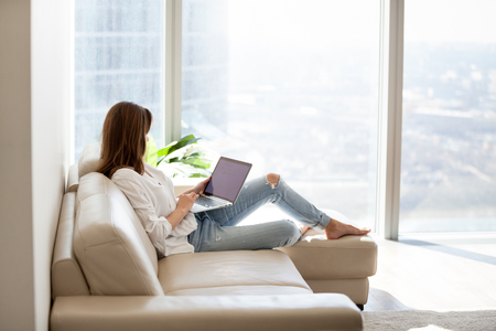 Photo for Relaxed woman using laptop in luxury home living room with big window, enjoying working, internet shopping, checking social network, reading news or communicating online with computer sitting on sofa - Royalty Free Image