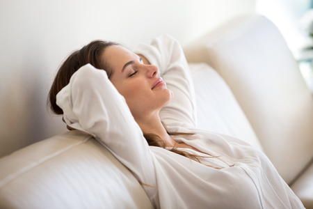 Foto de Calm millennial woman relaxing on soft comfortable sofa meditating or having daytime nap, carefree lazy girl breathing fresh air enjoying no stress free peaceful weekend morning resting on couch - Imagen libre de derechos
