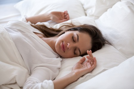 Foto de Sleeping woman enjoying healthy nap in cozy bed in the morning, millennial girl relaxing on soft pillow and comfortable mattress with white cotton sheets sleeping well and having enough rest concept - Imagen libre de derechos