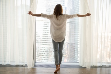 Foto de Rear view at rich woman standing looking out of full-length window of luxury modern apartment or hotel room opening curtains in the morning enjoying sunlight and city skyscrapers view feeling happy. - Imagen libre de derechos