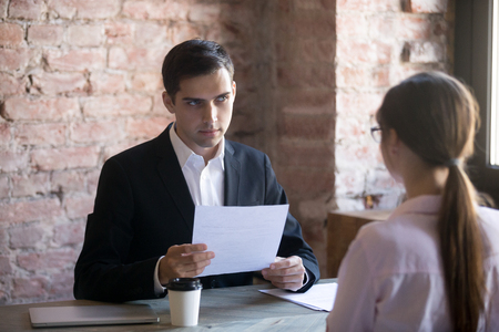 Photo for Serious HR manager interviewing young woman student in the office. Serious male wearing suit holding curriculum vitae and looking at candidate, woman sitting her back to camera. - Royalty Free Image