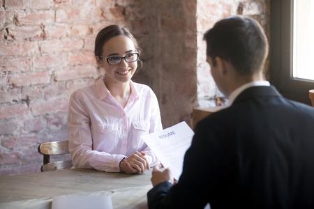 Photo for HR manager interviewing young smiling woman student in the office. Male wearing suit holding curriculum vitae sitting. Positive atmosphere, successfully passing the interview, confident girl - Royalty Free Image