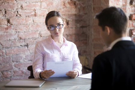 Photo for Serious HR young manager woman interviewing male in the office. Suspicious female holding curriculum vitae and looking at candidate, man sitting back to camera. Bad first Impression, failed interview - Royalty Free Image