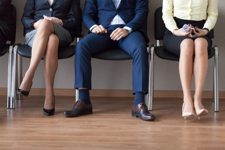 Photo pour Business people sitting in chairs in queue waiting for their turn for job interview. Group of candidates for one position to company. Human resources, hr, recruitment concept. People legs close up - image libre de droit