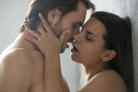 Photo for Close up of sensual millennial couple enjoying hot foreplay standing near wall, passionate lovers kissing and caressing, touching and teasing each other before making love, man and woman have intimacy - Royalty Free Image