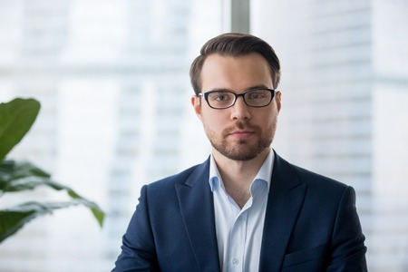 Photo for Portrait of serious millennial businessman wearing glasses looking at camera, headshot of concentrated confident male worker or director posing in modern office, making photo or picture near window - Royalty Free Image