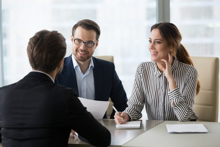 Foto de Smiling diverse HR managers satisfied about male job employee, have positive first impression of candidate, happy employers listen to applicant at interview excited of candidature. Recruitment concept - Imagen libre de derechos