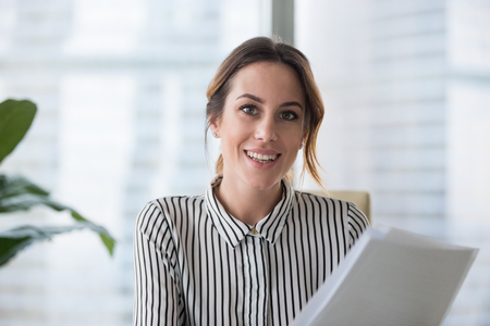 Photo for Portrait of smiling millennial businesswoman holding documents looking at camera, headshot of happy woman worker or female ceo posing with paperwork making picture at corporate photoshoot. - Royalty Free Image