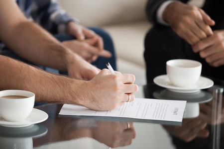 Photo for Close up of husband sign contract with wife sitting next to him supporting, couple put signature on document buying first home together when meeting with realtor or broker or closing deal with counsel - Royalty Free Image