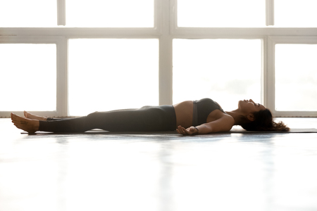Photo pour Young sporty attractive woman practicing yoga, doing Dead Body exercise, Savasana, Corpse pose, working out, wearing sportswear, grey pants, top, indoor full length, at yoga studio, side view - image libre de droit