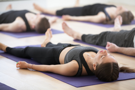 Photo pour Group of young sporty people practicing yoga lesson, doing Dead Body, Savasana, exercise Corpse pose, working out, indoor, students training in club, studio close up. Well-being concept - image libre de droit