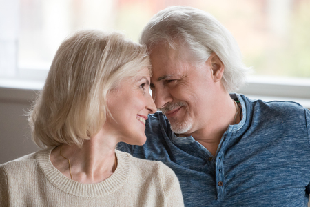 Photo pour Happy middle aged romantic couple touching noses having fun enjoying sincere love feelings together, smiling senior older family bonding looking at each other, mature man and woman dating concept - image libre de droit