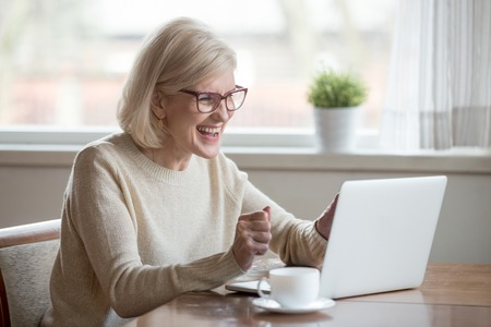 Foto de Happy mature middle aged elderly business woman winner excited by reading good news looking at laptop, glad senior older lady watching celebrating online bid bet win or great result victory concept - Imagen libre de derechos
