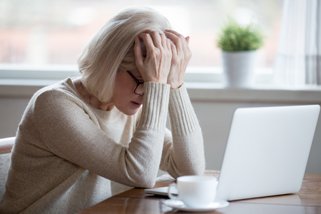 Foto de Upset depressed mature middle aged woman in panic holding head in hands in front of laptop frustrated by bad news, online problem or being fired by email feeling desperate shocked exhausted concept - Imagen libre de derechos