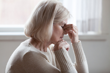 Foto de Fatigued upset middle aged older woman massaging nose bridge feeling eye strain or headache trying to relieve pain, sad senior mature lady exhausted depressed weary dizzy tired thinking of problems - Imagen libre de derechos