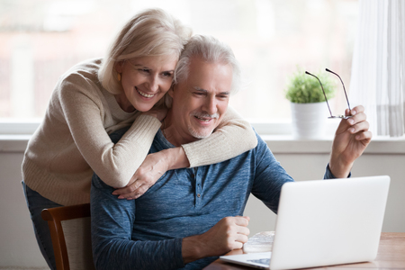 Foto de Senior middle aged happy couple embracing using laptop together, smiling elderly family reading news, shopping online at home, older people and computer or good vision after laser correction concept - Imagen libre de derechos