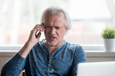 Foto de Angry furious senior mature man caller arguing talking on the phone disputing complaining about problems with laptop, mad emotional male shouting speaking by mobile calling customer support - Imagen libre de derechos
