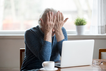 Foto de Fatigued senior mature man feels tired from computer rubbing dry irritated eyes to relieve pain or crying frustrated upset, old middle aged male suffering from eyestrain after long laptop use concept - Imagen libre de derechos