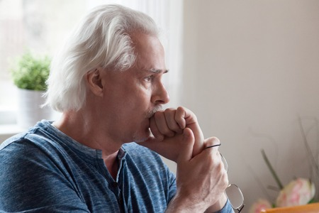 Foto de Worried serious mature senior man feeling melancholic anxious about problems making difficult decision, upset thoughtful sad middle aged old male looking away thinking of loneliness and depression - Imagen libre de derechos