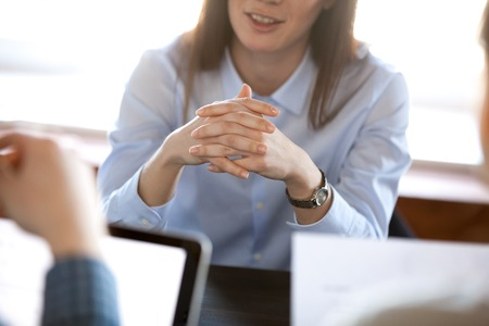 Photo pour Smiling woman attentively listening to partners concentrated on business negotiations, nonverbal communication concept, focus on locked crossed fingers, clenched hands gesture close up view - image libre de droit