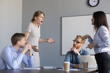Foto de Business women colleagues disputing arguing at corporate office meeting, mad angry shocked female employee disagree with coworker blaming for bad work, conflict and rivalry at workplace concept - Imagen libre de derechos