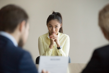 Foto de Nervous young Asian job applicant wait for recruiters question during interview in office, worried intern or trainee feel stressed applying for open position, meeting with hr managers. Hiring concept - Imagen libre de derechos
