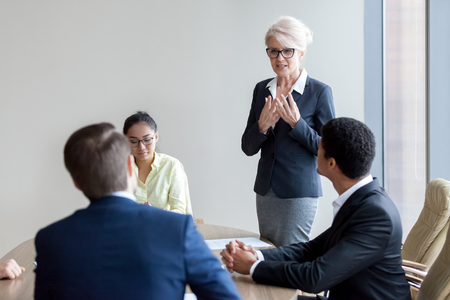 Photo for Middle aged female employee standing express her point of view to colleague at meeting, woman worker talk making speech, congratulating coworker or complimenting for work results at briefing - Royalty Free Image