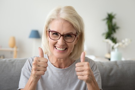 Foto de Excited mature woman in glasses sit on couch at home showing thumbs up satisfied with service, smiling elderly female make like gesture recommending something, satisfied with choice or decision - Imagen libre de derechos
