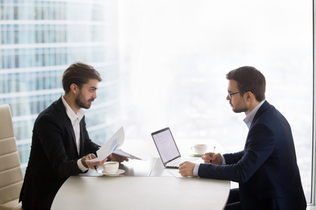 Photo for Two caucasian men sitting in front of each other at the table and discussing project results. Partners or manager and subordinate conduct performance evaluation appointment in office or meeting room - Royalty Free Image