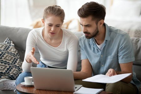 Foto de Frustrated married couple has financial problems wife and husband received bad news from bank about debt high taxes. Millennial woman and man reading mail on laptop holding paper letter domestic bill - Imagen libre de derechos