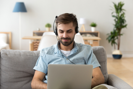 Photo pour Millennial man sitting on couch in living room at home. Satisfied male studying chatting online using computer and headset watching educational video, learning foreign languages on internet concept - image libre de droit