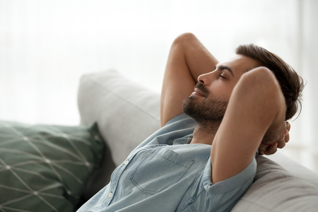 Photo for Close up side view serene man smiling sitting on couch at home. Male has a break after work or study closing eyes putting hands behind head relaxing thinking, feels happy breathing fresh air concept - Royalty Free Image