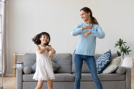 Foto de Cheerful mother little daughter standing in living room at home moving dancing to favourite song together. Child have fun with elder sister nanny or loving mother active leisure and lifestyle concept - Imagen libre de derechos