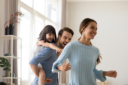 Foto de Young happy father laughing carrying on back piggybacking little daughter catching mum playing with diverse family having fun together. Kid enjoying active game with parents in living room at home - Imagen libre de derechos