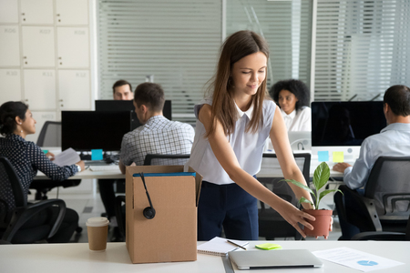 Photo for Smiling hired female company employee unpacking box with personal belongings at workplace on first working day in shared office, happy intern or newcomer got new job excited to start work concept - Royalty Free Image