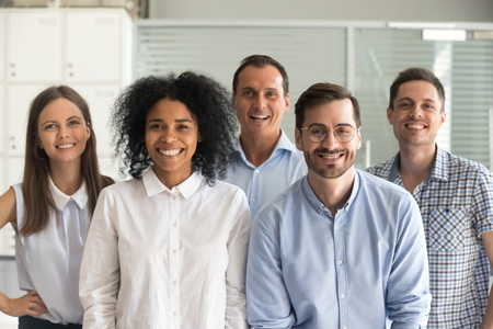 Photo pour Smiling diverse office workers group, happy multiracial professional members employees looking at camera, motivated staff business people posing together, multi-ethnic workforce sales team portrait - image libre de droit