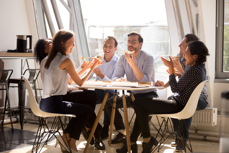 Photo pour Friendly happy diverse team workers talking laughing eating pizza together in office, cheerful workers staff group chatting sharing meal enjoying having fun at work, good relations at lunch break - image libre de droit