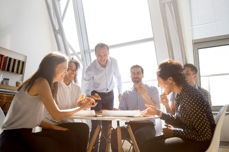 Photo pour Cheerful diverse team people workers students laughing at funny joke while eating pizza together, friendly multi-ethnic colleagues group talking enjoying having fun and corporate lunch in office room - image libre de droit