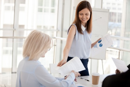 Photo pour Smiling millennial female mentor or coach give handouts to employees at teambuilding or training in office, young woman share paperwork plan or report to colleagues at briefing or business meeting - image libre de droit