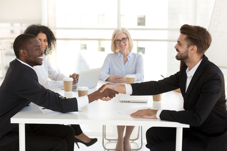 Photo for Smiling diverse business partners shake hand closing deal at office meeting, multiethnic excited businessmen handshake making agreement, starting cooperation after successful negotiation - Royalty Free Image