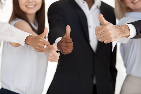 Foto de Close up of multiethnic happy workers or employees show thumbs up sign satisfied with career or company choice, smiling diverse business clients or customers gesture great positive experience - Imagen libre de derechos
